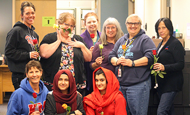 Kent-Meridian female office staff and Afghan Student Association students with roses
