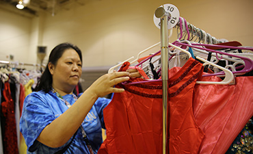 Volunteer helps organize prom dresses.