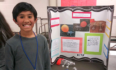 Student smiles with science project.