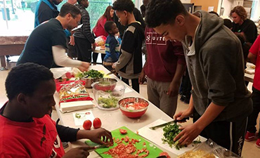 Students prepare food at community event.
