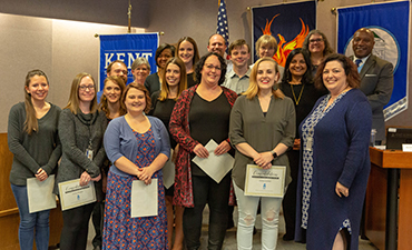 Teacher recognized at board meeting.