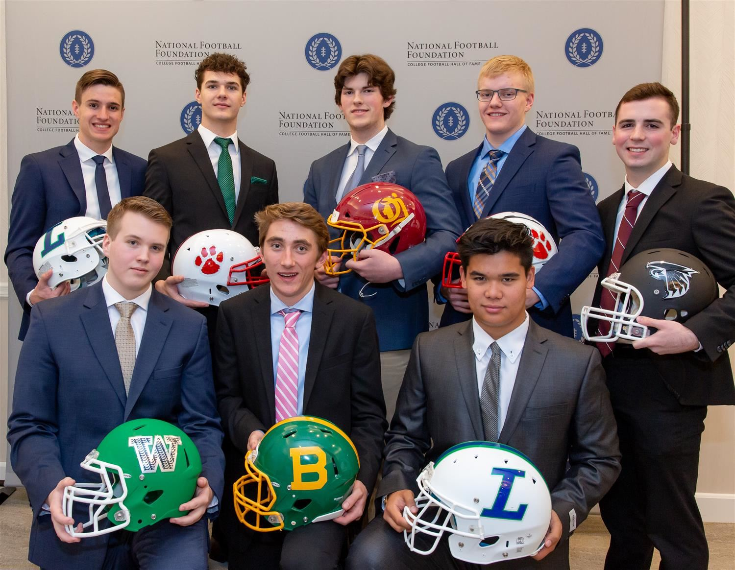 Students pose with their football helmets.