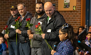 Students give roses to veterans during an assembly.