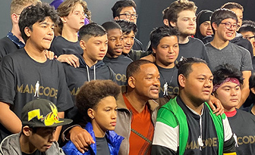 Students smile with Will Smith.